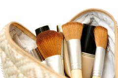 Open cosmetic bag with makeup brushes and cosmetics Stock Photo