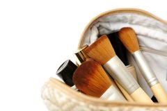 Open cosmetic bag with makeup brushes and a set of cosmetics Stock Photos