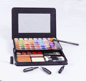 Open cosmetics compact. Containing a collection of make-up including blusher, lipstick, eye shadow in the colours of the rainbow and applicators with a small Royalty Free Stock Photo