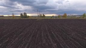 Field, road and clouds. Open country. The drone removes from low height. Moves along the field. In a shot the power line is visible. The road is also visible. On stock video footage
