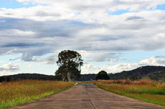 Open country road ahead with clouds & fields. A quiet deserted Australian country road in a remote part of Queensland in the Scenic Rim. The road is part paved Royalty Free Stock Photos
