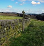 Open countryside with direction sign next to a dry stone wall. With green fields and mooland in the distance in yorkshire england royalty free stock image