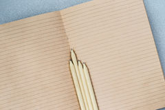 Open craft notebook and wooden Pencils, top view. Place for text, concept of starting school, back to school, education. Education, workplace Stock Photography