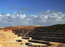 Open cut mine. Terraces with blue sky and clouds in the background Royalty Free Stock Photo
