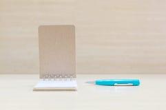 Open de notaboek van de close-upoppervlakte met blauwe pen op vaag bruin houten bureau en houten muur geweven achtergrond met exe Stock Foto