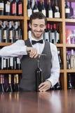 Open de Wijnfles van barmanusing corkscrew to stock foto