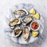 Open desvainó ostras con el limón y la salsa picante Foto de archivo libre de regalías