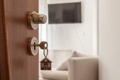 Open deur aan een nieuw huis Deurhandvat met sleutel en gestalte gegeven huis keychain Onroerende goederen hypotheek, investering stock foto's