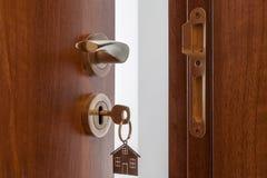Open deur aan een nieuw huis Deurhandvat met sleutel en gestalte gegeven huis keychain Onroerende goederen hypotheek, investering royalty-vrije stock afbeeldingen