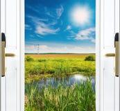 Open deur met een mening van groene weide die door heldere zonneschijn wordt verlicht Royalty-vrije Stock Afbeeldingen