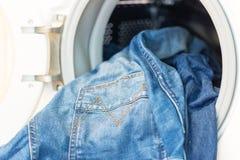 Open deur in wasmashine met binnen jeans Stock Afbeelding