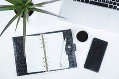 Open diary alongside a potted plant and mobile Royalty Free Stock Photography