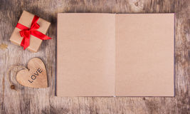 Open diary with blank pages from recycled paper, gift box with a bow and a wooden heart.  Copy space. Valentine`s Day. Royalty Free Stock Photo