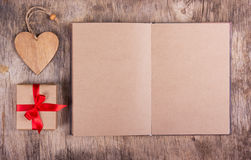 Open diary with blank pages from recycled paper, gift box with a bow and a wooden heart. Copy space. Valentine`s Day. Stock Image