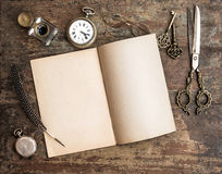 Open diary book and antique writing tools on wooden background Royalty Free Stock Images