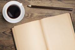 Open diary and coffee cup on old wooden table top Stock Photo