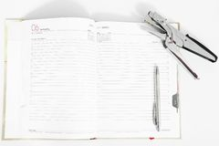Open diary with pen and stapler. On the white background stock image
