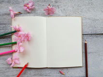 open diary and pencil pink flower on wood background Stock Photos
