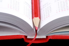 Open diary with red pencil. Royalty Free Stock Images