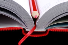 Open diary with red pencil on white. Royalty Free Stock Photos
