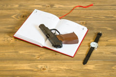 Open diary on the table and a gun on him Royalty Free Stock Image