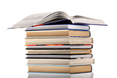 Open dictionary on top of book stack isolated on w Royalty Free Stock Photo