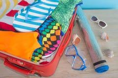 Open die koffer voor het reizen wordt ingepakt Koffer met verschillende die dingen op reis worden voorbereid Stock Afbeeldingen