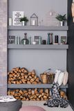 Open dining room interior with firewood, shelves on the grey wall and wooden log wall decoration for warm cozy Stock Photos