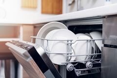 Open dishwasher with clean dishes at home kitchen Royalty Free Stock Photo