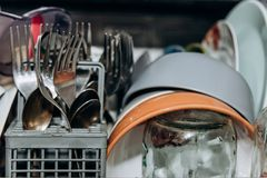 Open dishwasher close up clogged with clean washed dishes. dry cutlery closeup. spoons forks. mugs, plates. household appliances royalty free stock photography