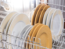 Open dishwasher. With different coloured ans sized plates Royalty Free Stock Photography