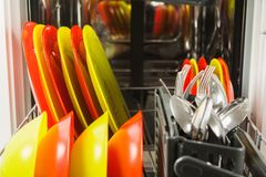 Open dishwasher with fresh clean dish and flatware. Closeup view royalty free stock photo