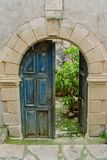 Open door. A blue door with a marble arch opens into a courtyard with green garden Royalty Free Stock Photo