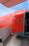 Open door of big civil airplane painted in red royalty free stock photos
