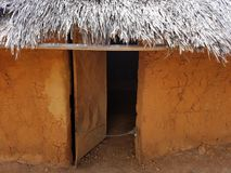 Open door of brown and red adobe building with straw roof. Open door of brown and red adobe or clay building with straw roof Royalty Free Stock Image