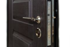 Open armored door. Door lock, Dark brown door closeup. Modern interior design, door handle. New house concept. Real estate. Open door. Door lock, Dark brown Royalty Free Stock Images