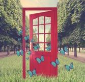 Open door in green garden and flying butterflies Royalty Free Stock Images