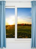 Open door with green meadow illuminated by bright sunshine Royalty Free Stock Image