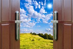 Open door with  of green meadow illuminated by bright sunshine Royalty Free Stock Photo