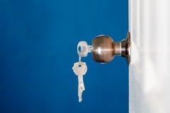 Open door with keys, key in keyhole Stock Photo