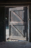 Open door in a neglected barn. The old wooden door of the abandoned barn is open Royalty Free Stock Photos