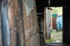 Open door of an old rotten wooden shed royalty free stock photography