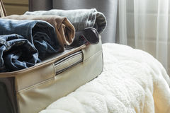 Open door and open suitcase with clothes on the bed. Open door and open suitcase with clothes stock photography
