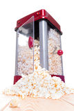 Open door popcorn popper with food pouring out. Open door of red and gray popcorn popper with food pouring out on light wooden table with white background Royalty Free Stock Photo