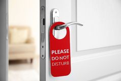 Open door with sign PLEASE DO NOT DISTURB. On handle at hotel Stock Photography