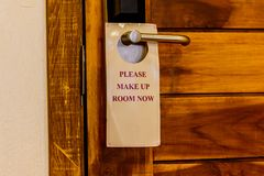Open door with sign PLEASE MAKE UP ROOM on handle at hotel in th Royalty Free Stock Photo