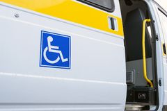 The open door of a specialized vehicle for people with disabilities. White bus with a blue sign for the disabled. Yellow bar and. White bus with a blue sign for stock photos