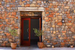 Open door and  stone mediterranean wall(Greece). Open door and terracotta pots with young olive tree against a stone mediterranean wall(Greece Stock Photography
