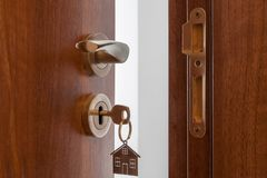 Open door to a new home. Door handle with key and home shaped keychain. Mortgage, investment, real estate, property and new home royalty free stock images