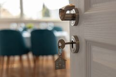 Open door to a new home. Door handle with key and home shaped keychain. Mortgage, investment, real estate, property and new home